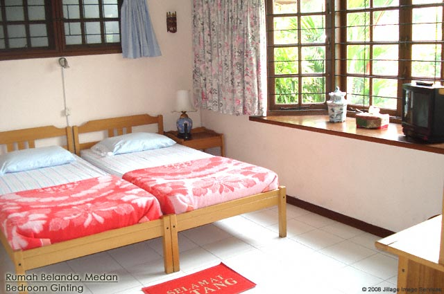 Rumah Belanda bedroom Ginting with to single beds, working area, wardrobe